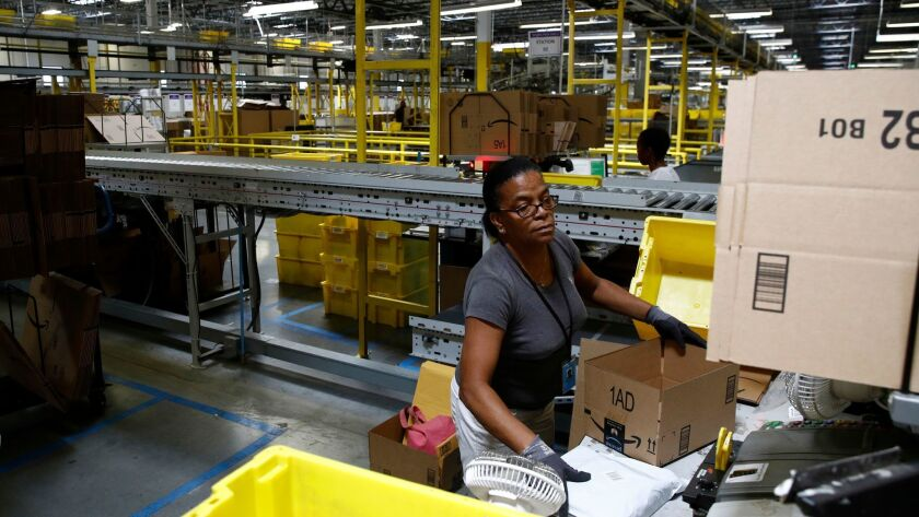 Myrtice Harris packages products for shipment at an Amazon fulfillment center in Baltimore. The nation's largest online retailer said it sold more than 200,000 toys in the first five hours of Black Friday.