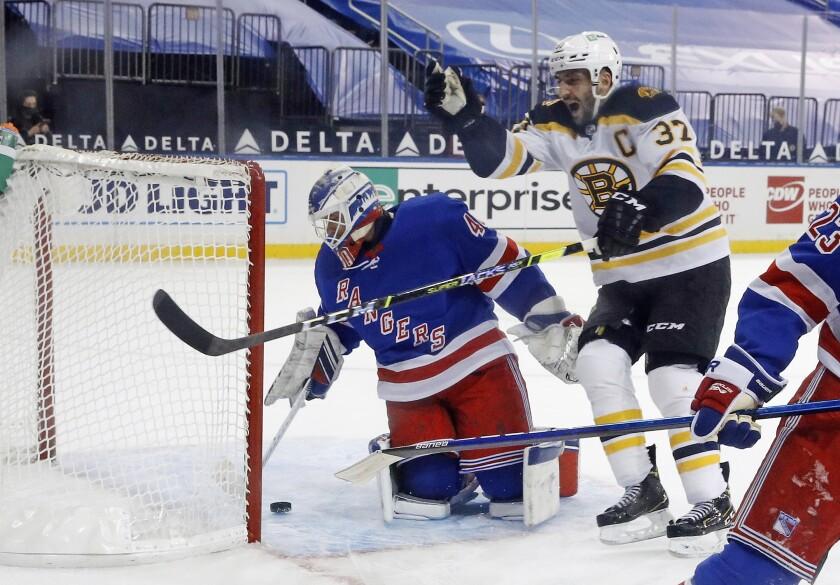 Boston Bruins' Patrice Bergeron (37) celebrates the overtime goal by Bruins' Brad Marchand (not shown) against New York Rangers' Alexandar Georgiev (40) in an NHL hockey game Wednesday, Feb. 10, 2021, in New York. (Bruce Bennett/Pool Photo via AP)