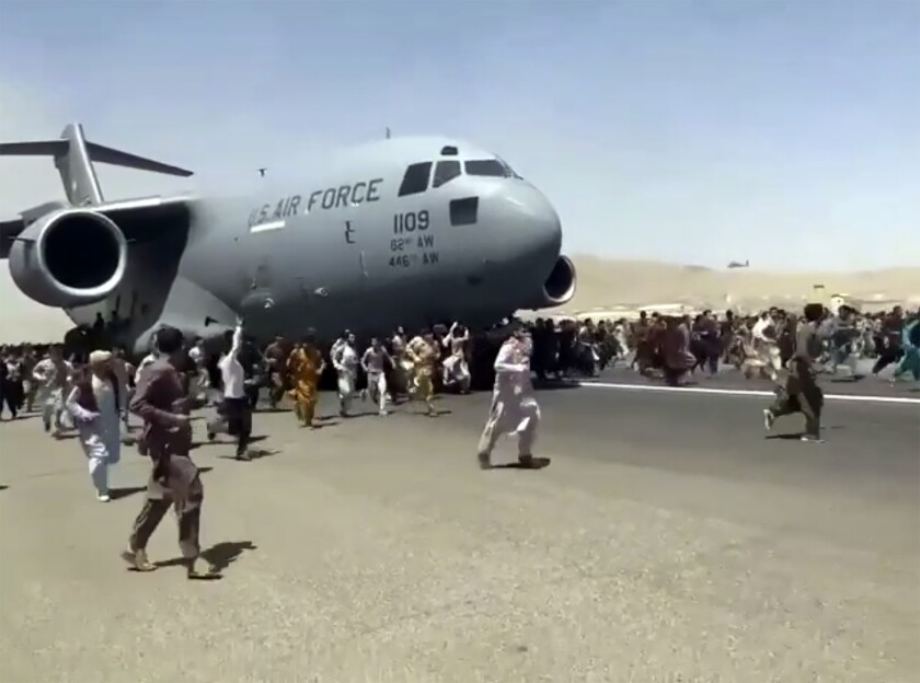 Hundreds of people run alongside a U.S. Air Force C-17 transport plane as it moves down a runway of the Kabul airport.