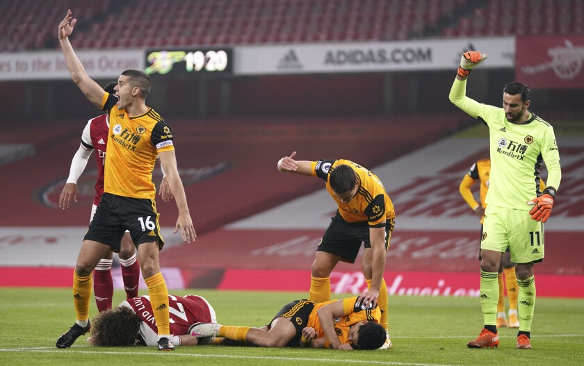 Los jugadores piden auxilio luego del choque de cabezas entre David Luiz de Arsenal y Raúl Jiménez de Wolverhampton.