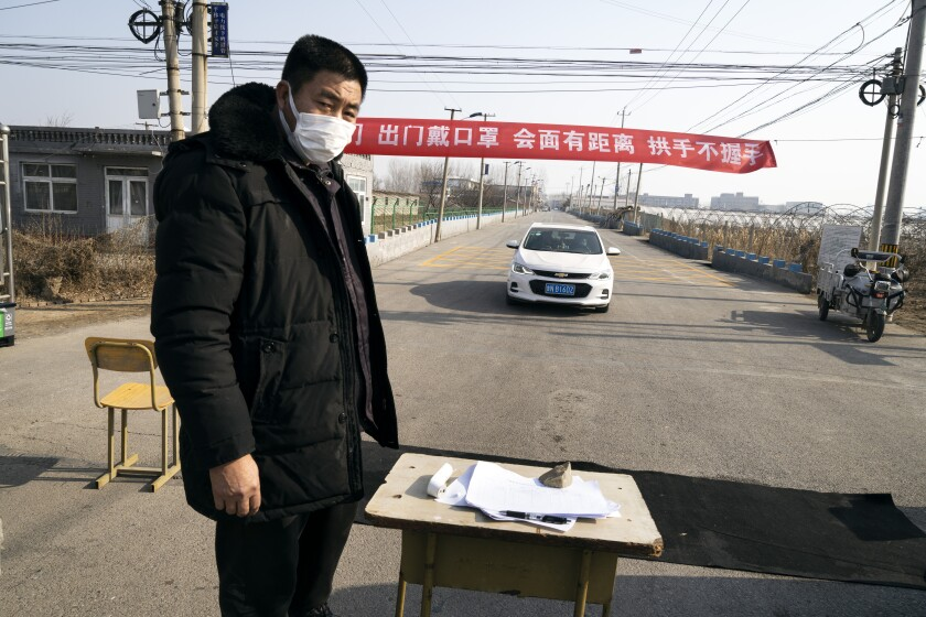 The street to a Chinese village is blocked as a man keeps track of people entering by using a thermometer and a paper list on the table.