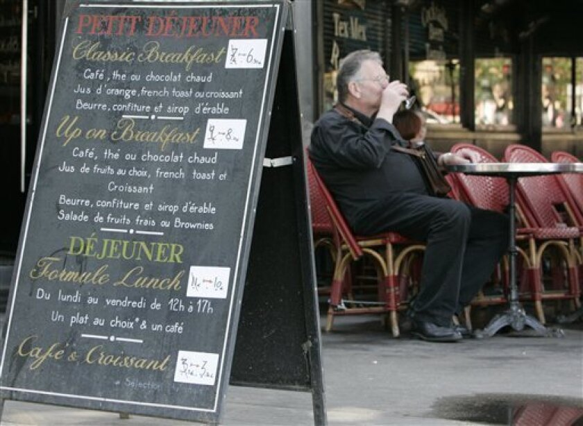 A man drinks at a cafe where prices were modified, Wednesday July 1, 2009 in Paris. France's restaurant bills could start looking a little slimmer thanks to a nearly fourfold drop in sales taxes. The measure allowing a reduction of VAT, or value-added tax, from 19.6 percent to 5.5 percent went into effect Wednesday.(AP Photo/Jacques Brinon)