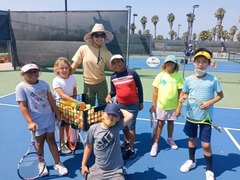 City Heights kids enjoying tennis on a court in August.