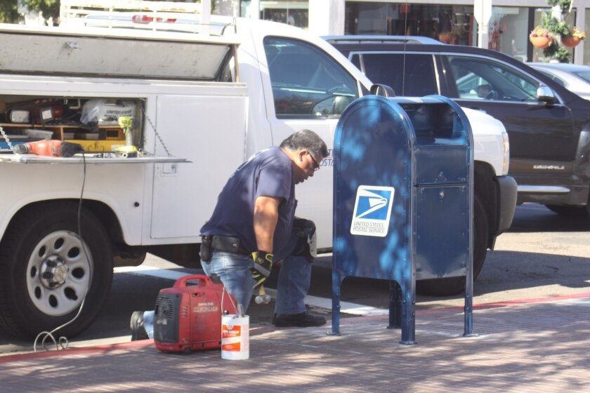 A USPS worker replaces the collection box at the corner of Girard Avenue and Silverado Street, Dec. 31.