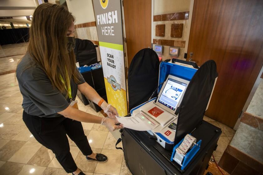 A woman casts a ballot at a machine.