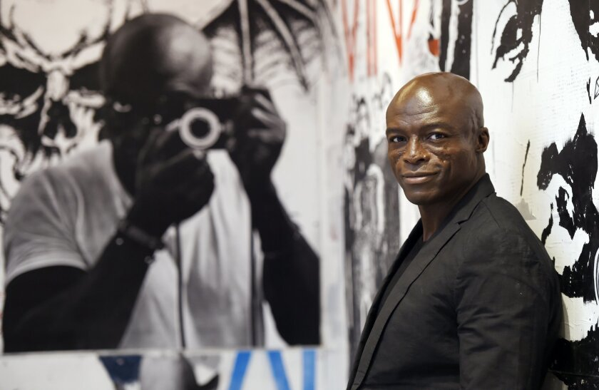 """In this Monday, Oct. 5, 2015 photo, singer/songwriter Seal poses in front of a mural of musicians including himself at left at Warner Bros. Records in Burbank, Calif.  """"Seal 7"""" is the artist's first new music in five years: an album about love, heartbreak and healing. (Photo by Chris Pizzello/Invis"""