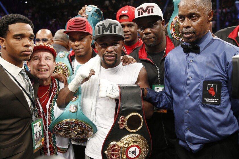 Floyd Mayweather Jr., center, stands with referee Kenny Bayless, right, after defeating Andre Berto for the WBC/WBA welterweight titles.