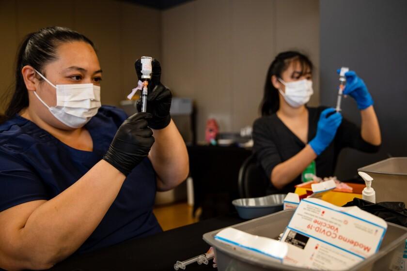 La técnica farmacéutica Anna-Marie Lumanla y la farmacéutica Cinny Wong preparan las dosis de la vacuna