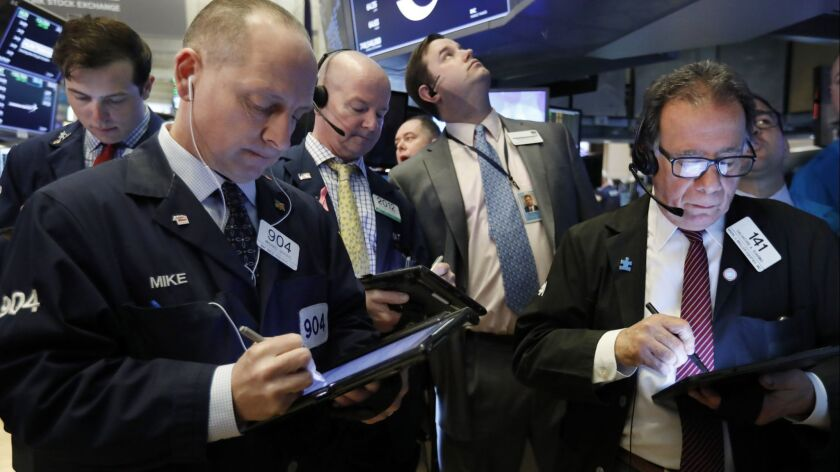 FILE- In this March 13, 2019, file photo traders gather at the post that handles Oaktree Capital Gro