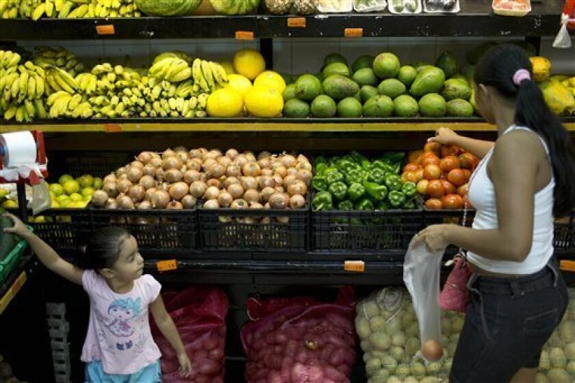 A woman shops for tomatoes with her daughter at a supermarket in Rio de Janeiro, Brazil, Thursday, April 11, 2013. A longer-than-usual rainy season, high fuel prices and superheated demand have combined to send prices for the beloved vegetable soaring, and consumers are seeing red. (AP Photo/Felipe Dana)
