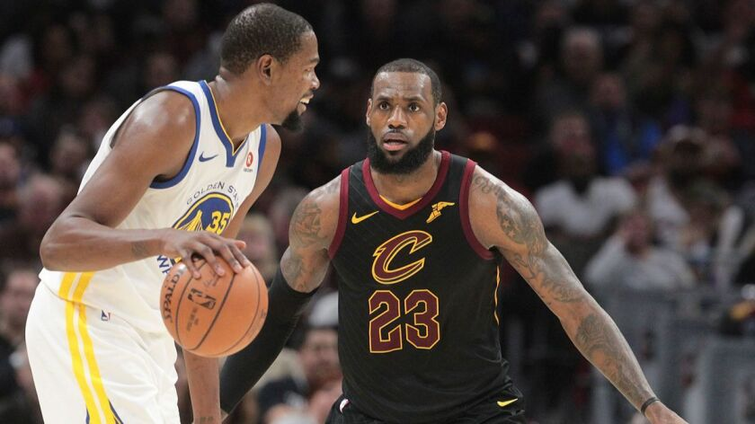 Cleveland Cavaliers forward LeBron James defends Golden State Warriors forward Kevin Durant in the third quarter on Jan. 15. The Cavaliers lost to the Warriors 118-108.