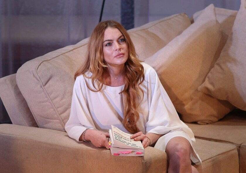 """FILE - In this Tuesday, Sept. 30, 2014 file photo, U.S actress Lindsay Lohan performs a scene from the play, """"Speed the Plow,"""" during a photocall at the Playhouse Theatre in central London. A prosecutor said Wednesday, May, 27, 2015, that it appears Lohan has completed the community service terms of her sentence in a 2012 reckless driving case. A judge will determine on Thursday, May 28, 2015, whether Lohan has completed her sentence, which would release her from probation in Los Angeles for the first time in nearly eight years. (Photo by Joel Ryan/Invision/AP, File)"""