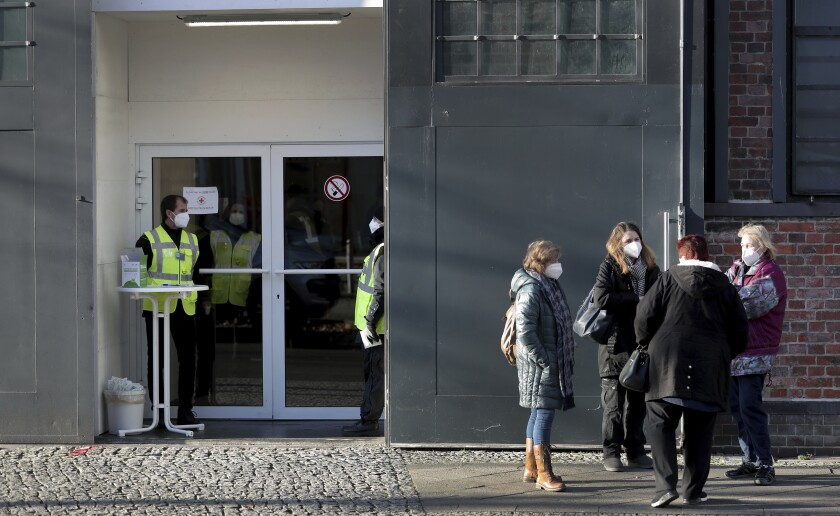 People gather outside a COVID-19 vaccination center in Berlin on Wednesday.