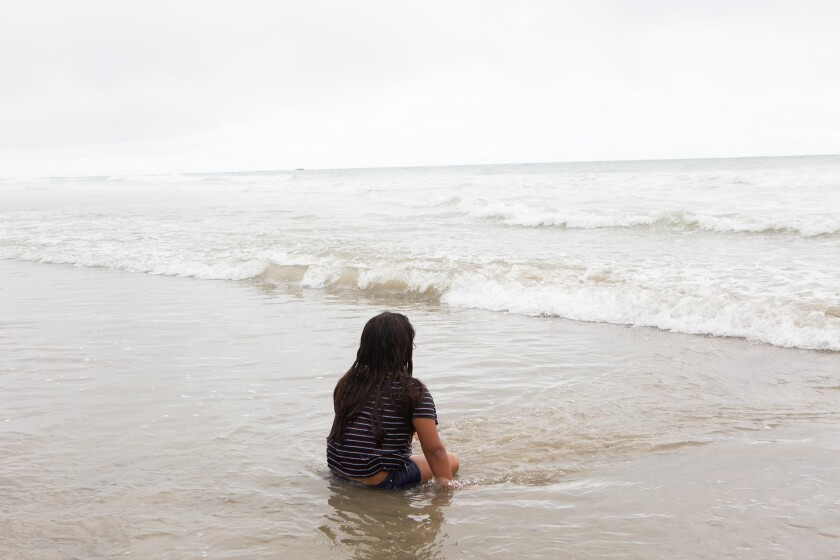 Jocelyn Corado, 8, waits for the next set of waves near the San Clemente Pier on Monday.