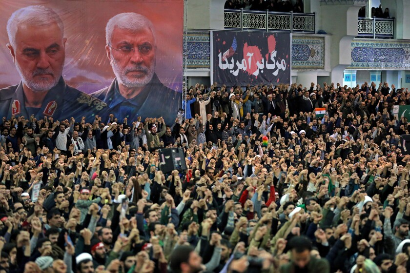 """In this photo released by the official website of the office of the Iranian supreme leader, worshippers chant slogans during Friday prayers ceremony, as a banner show Iranian Revolutionary Guard Gen. Qassem Soleimani, left, and Iraqi Shiite senior militia commander Abu Mahdi al-Muhandis, who were killed in Iraq in a U.S. drone attack on Jan. 3, and a banner which reads in Persian: """"Death To America, """"at Imam Khomeini Grand Mosque in Tehran, Iran, Friday, Jan. 17, 2020. Iran's supreme leader said in his sermons President Donald Trump is a """"clown"""" who only pretends to support the Iranian people but will """"push a poisonous dagger"""" into their backs, as he struck a defiant tone in his first Friday sermon in Tehran in eight years. (Office of the Iranian Supreme Leader via AP)"""