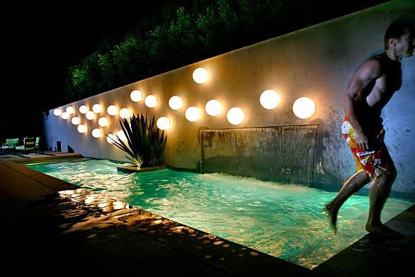 """Pool season is here, and we've got a peek at some backyard beauties: a Fullerton lap pool that only seems to go on forever, as well as a vintage design in Baldwin Hills that brims with 1960s chic. First up, however: pool as backyard sculpture. As writer Emily Young discovered when she visited this Pasadena property, landscape designer Anthony Exter drew on his interest in the circular motifs of French painter Robert Delaunay. """"I laid out the bubbles to look like they're concentrated near the waterfall and then more spread out as if dispersed by a breeze,"""" he says of the light globes. That's owner Jimmy Wilson emerging from the water. Back to L.A. at Home"""