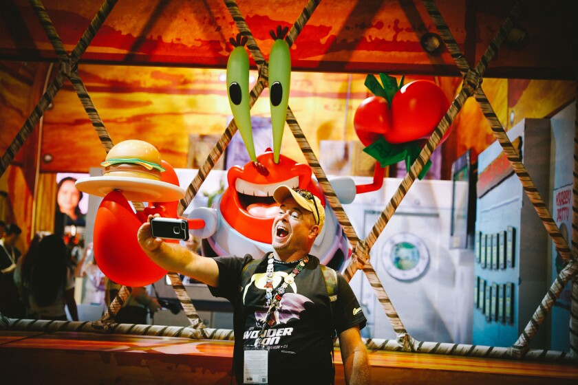 A fan poses with the character Mr. Krabs at Comic-Con in San Diego
