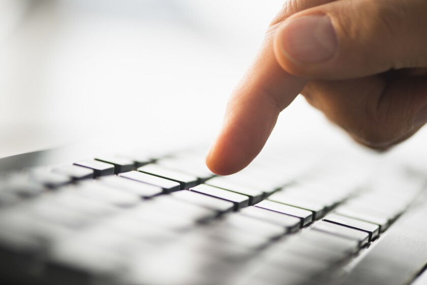 A hand points at a computer keyboard