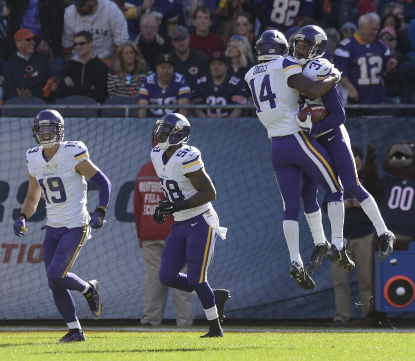 Minnesota Vikings wide receiver Stefon Diggs (14) celebrates with cornerback Marcus Sherels (35) after his first-half touchdown during an NFL football game against the Chicago Bears in Chicago, Sunday, Nov. 1, 2015. (Mark Black/Daily Herald via AP) MANDATORY CREDIT; MAGAZINES OUT