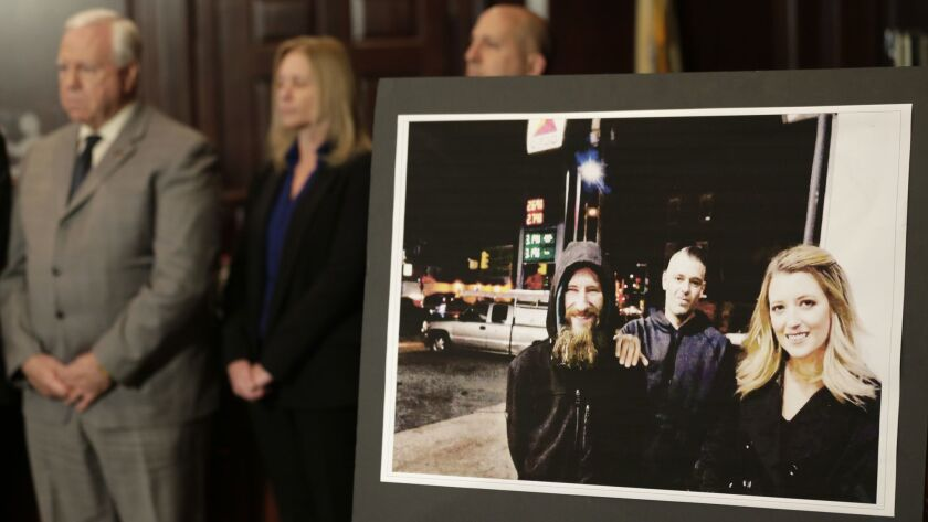 A picture of Katelyn McClure, right, Mark D'Amico, center, and Johnny Bobbitt Jr. is displayed durin