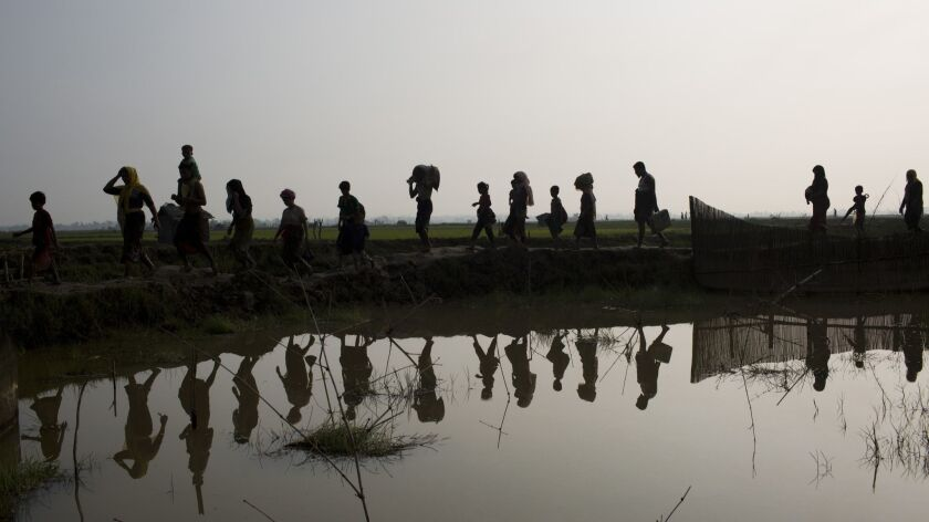 FILE - In this Sept. 5, 2017 file photo, members of Myanmar's Rohingya ethnic minority walk through