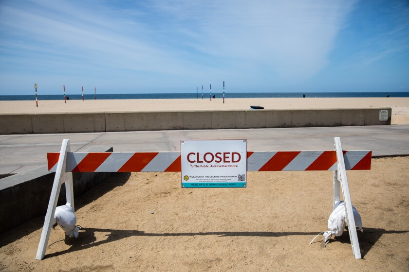Signs and barricades let people know of the closures of the Strand and the beach in Hermosa Beach earlier this year.