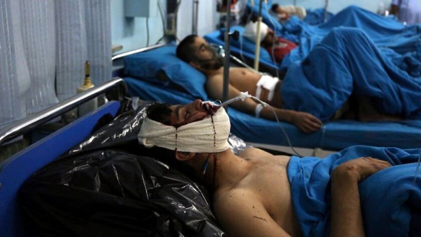 Injured men receive treatment at a hospital after a suicide bomber targeted a gathering of Muslim religious scholars in Kabul.