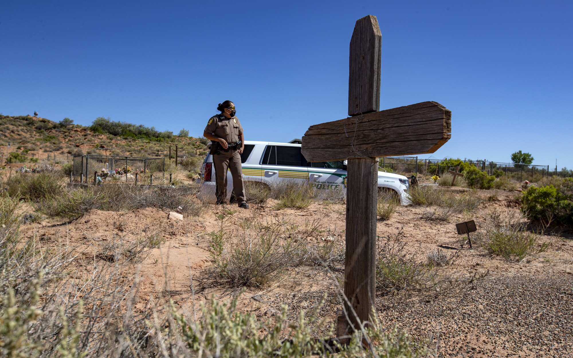 Navajo Nation Police Officer Carolyn Tallsalt looks out at dried sagebrush where her uncle George Billy was buried in April at the Tuba City Community Cemetery in Arizona. (Brian van der Brug / Los Angeles Times)