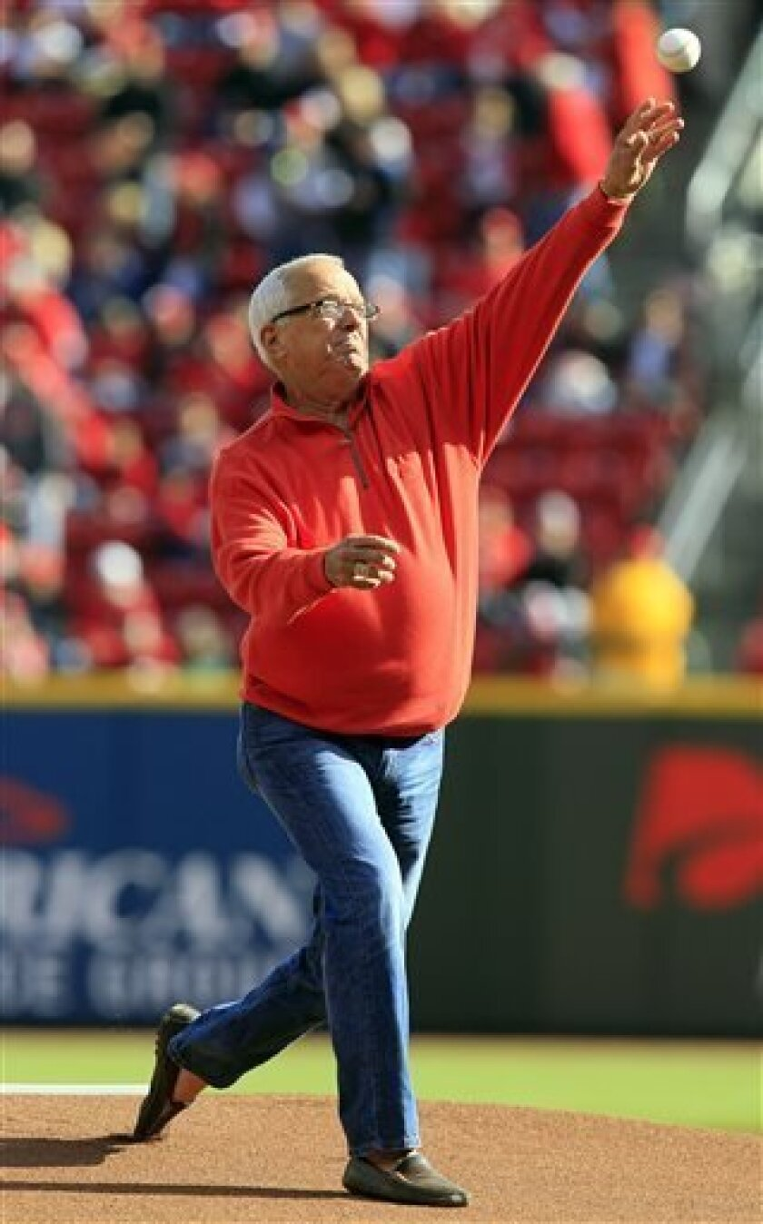 This Oct. 10, 2012, photo shows Cincinnati Reds broadcaster Marty Brennaman throwing out a ceremonial first pitch in Cincinnati. Brennaman says the Cincinnati Reds opening day festivities are unlike any other major league city. People are getting ready for Monday's events and the opening game with
