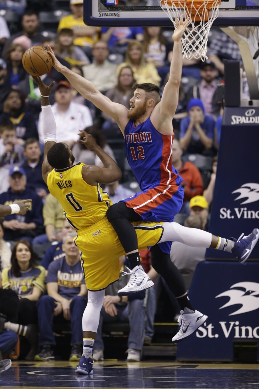 Detroit Pistons center Aron Baynes (12) blocks a shot by Indiana Pacers forward C.J. Miles (0) during the first half of an NBA basketball game in Indianapolis, Saturday, Feb. 6, 2016. (AP Photo/Michael Conroy)