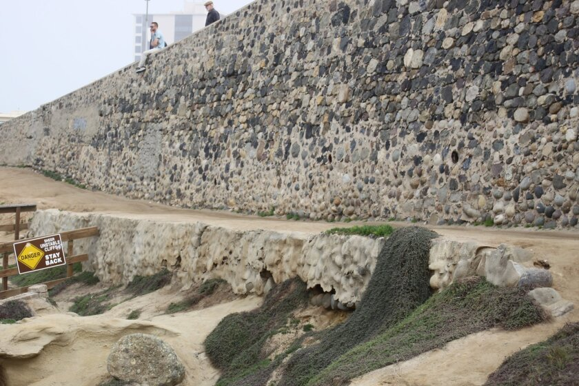 Erosion and foot traffic have created makeshift paths and damaged the retaining wall under the climbing wall.