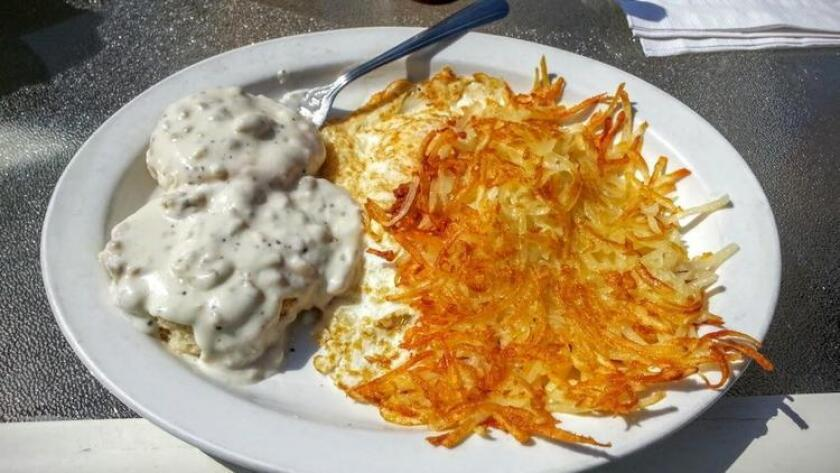 Biscuits smothered in sausage gravy with over medium eggs and hash browns at the 19th Hole Cafe.