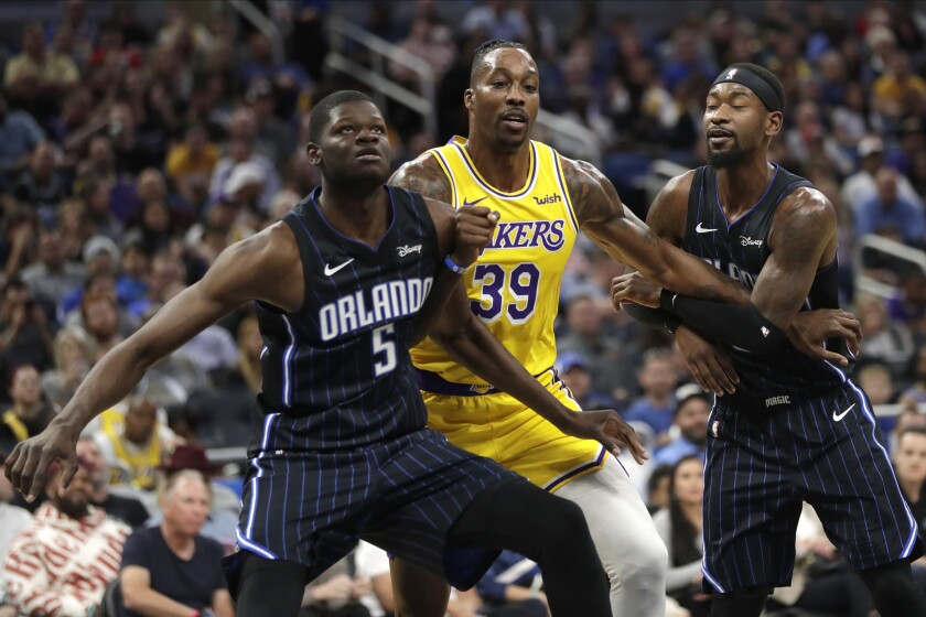 Lakers center Dwight Howard (39) battles Orlando's Mo Bamba (5) and Terrence Ross during their game Dec. 11, 2019, in Orlando.