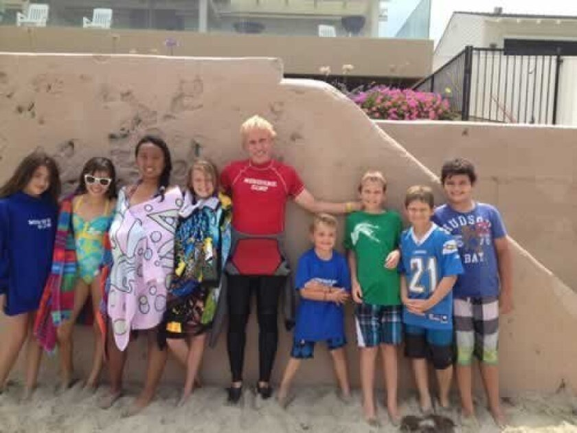 Mark Heinze poses with some of the students he teaches at Menehune Surf Camp.