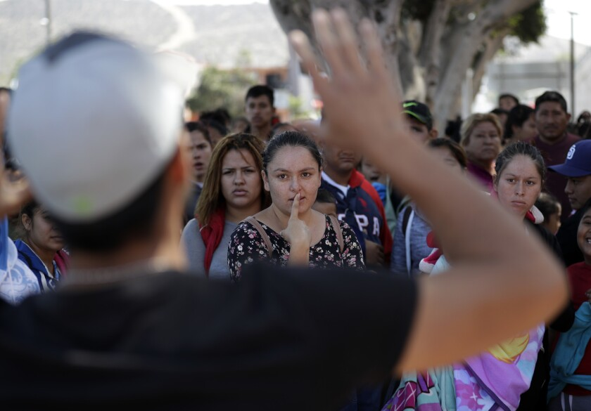 An organizer speaks to families June 13 as they wait to request political asylum in the United States, across the border in Tijuana, Mexico.