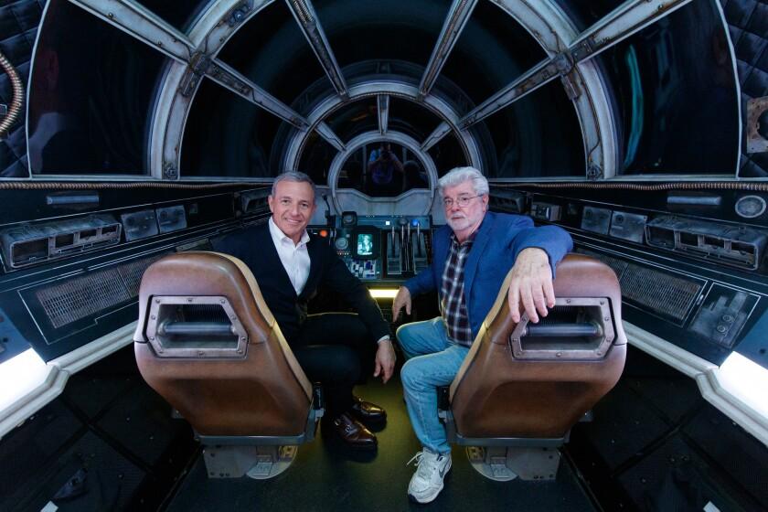 """El presidente de Disney, Bob Iger, y el cineasta George Lucas posan al interior de """"Millennium Falcon: Smugglers Run"""" en """"Star Wars: Galaxy's Edge"""" de Disneyland."""