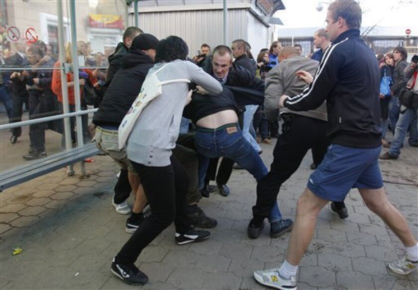 "People argue with a plainclothes policemen as he tries with others to detain a protester, center, during an action called ""Revolution via social network"" in Minsk, Belarus, Sunday, July 3, 2011. Participants in the protest action, Revolution thru Social Networks, are being detained in Minsk. According to the preliminary information, several dozens of people have been seized. (AP Photo/Sergei Grits)"