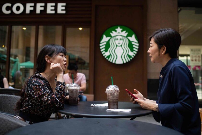 Women talk at a Starbucks in China