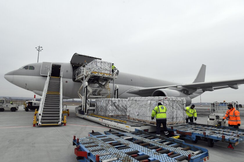 Boxes containing vaccines are unloaded from a Hungarian Airbus 330 cargo plane as the first batch of the vaccine against the new coronavirus produced by Sinopharm of China arrives at Budapest Liszt Ferenc International Airport in Budapest, Hungary, Tuesday, Feb. 16, 2021. The vaccine will not be used without its examination and approval by the National Public Health Center of Hungary. (Zoltan Mathe/MTI via AP)
