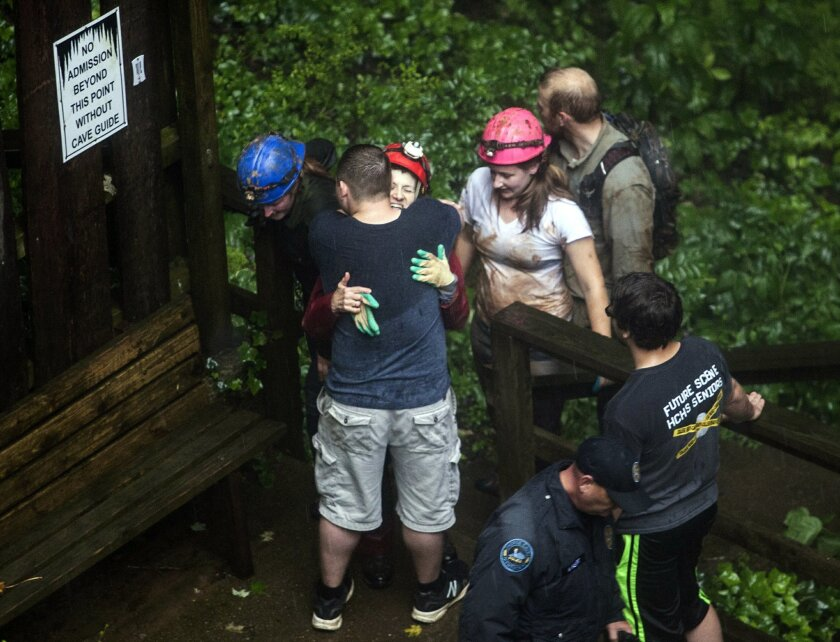 Tour guide Peggy Nims hugs a friend after she made it out of Hidden River Cave after officials said over a dozen people who were exploring the cave were trapped by rising water Thursday, May 26, 2016, in Horse Cave, Ky. The group waded through neck-deep water to get out, authorities said Thursday.