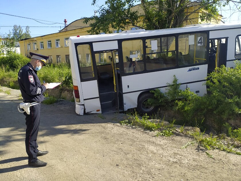 In this photo provided by Russian Interior Ministry, a Russian police officer stands near the bus which crashed into a bus stop in the town of Lesnoy about 1,350 kilometers (840 miles) east of Moscow, Russia, Thursday, June 10, 2021. A bus crashed into a bus stop in Russia's Sverdlovsk region on Thursday morning, killing six people and injuring 15 others, local officials said. The bus was carrying workers to a plant in the town of Lesnoy about 1,350 kilometers (840 miles) east of Moscow. (Russian Interior Ministry via AP)