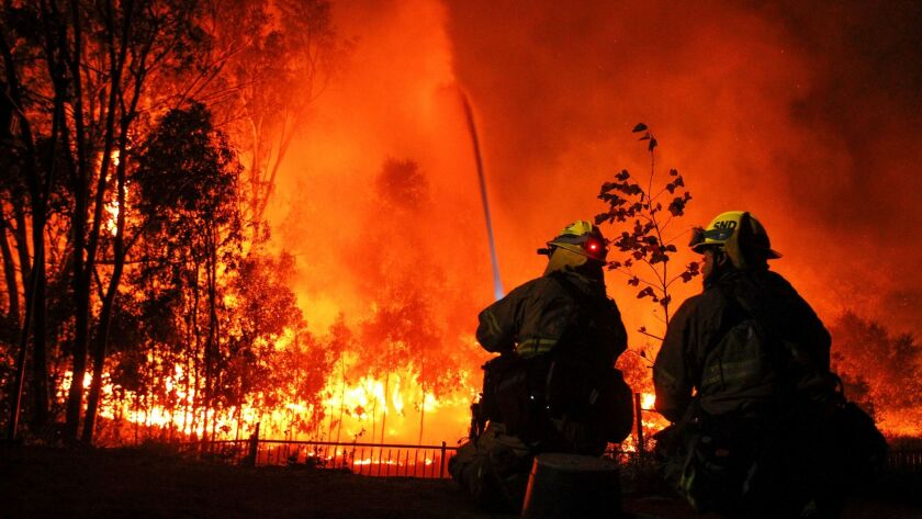 SAN DIEGO, December 7, 2017 | San Diego Fire and Rescue firefighters Corey Tang, hosing, and Steven