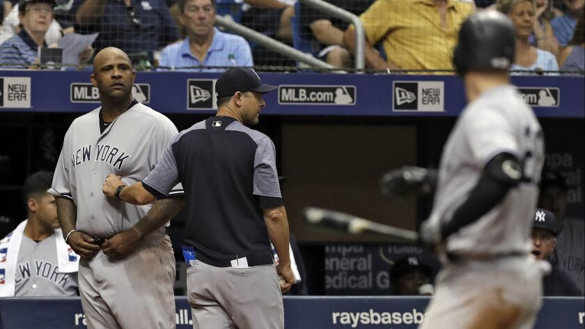 New York Yankees manager Aaron Boone, center, restrains starting pitcher CC Sabathia, left, after Tampa Bay Rays pitcher Andrew Kittredge threw behind Yankees batter Austin Romine, right, during the sixth inning.