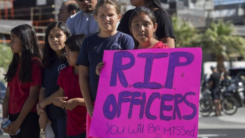 Fourth grade children from Katherine Finchy Elementary School pay respects outside funeral services for fallen Palm Springs Police officers Jose Gilbert Vega and Lesley Zerebny at the Palm Springs Convention Center on October 18, 2016 in Palm Springs.