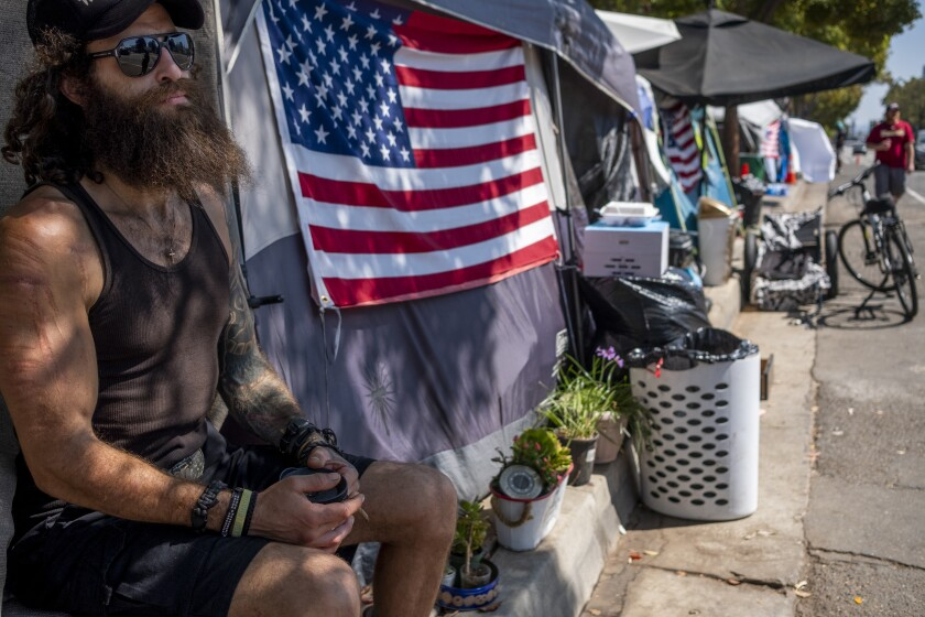Jonathan Garcia sits next to his tent in a homeless encampment outside the West L.A. Veterans Affairs facilities.