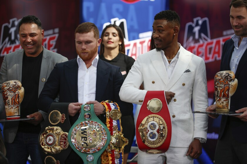 FILE - In this March 1, 2019, file photo, WBC and WBA middleweight world champion Canelo Alvarez, second from left, and IBF middleweight world champion Daniel Jacobs, second from right, pose with their title belts during a press conference in Mexico City. The moment won't be too big for Daniel Jacobs, of that he's certain. Not after going toe-to-toe with the fearsome Gennady Golovkin before dropping a narrow decision. Not after beating cancer that doctors were sure would end his career, if not his life. Canelo Alvarez will just be another obstacle in front of him when they meet Saturday night, May 4 in a middleweight title unification fight.