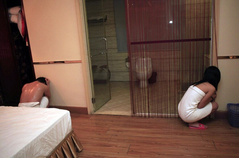 An alleged sex worker and client are shown during a raid on an entertainment center in Dongguan, in southern China's Guangdong province.