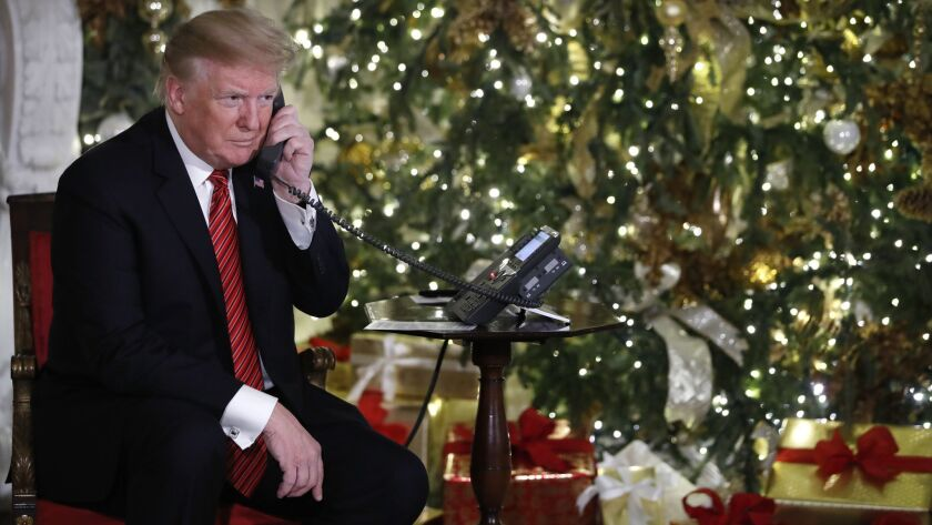 President Trump listens on the phone as he shares updates on Santa's movements from the North American Aerospace Defense Command's Santa tracker on Christmas Eve.