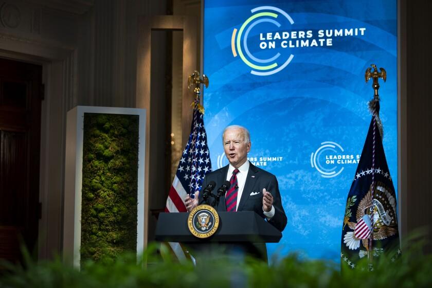 President Biden speaks before a backdrop reading Leaders Summit on Climate Change