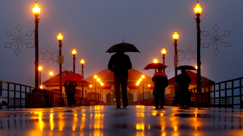 People stroll with their umbrellas on the Huntington Beach Pier during rain -- something that didn't occur too often in Southern California during an El Niño year.
